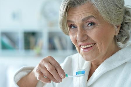 Portrait of happy senior woman brushing her teeth Stock Photo