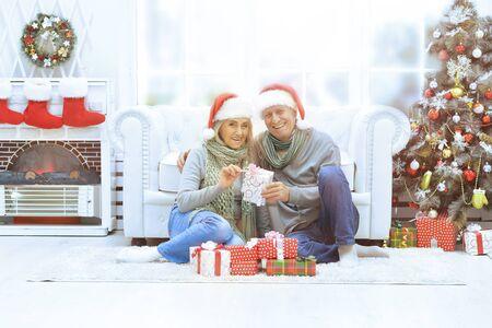 Happy senior couple celebrating Christmas at home, looking at the camera