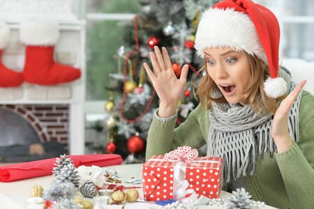 Portrait of exited woman with Christmas gift ar home