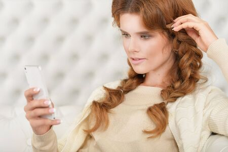 Portrait of beautiful young woman with smartphone at home