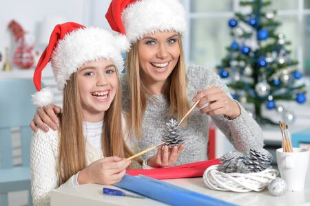 hapy: Portrait of  two hapy sisters in Santa hats preparing for Christmas Stock Photo