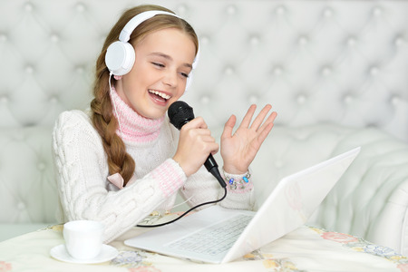 Preteen girl in white headphones singing karaoke