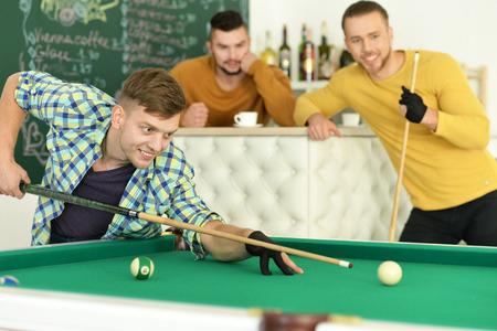 billiards halls: Portrait of three young handsome men play billiard Stock Photo