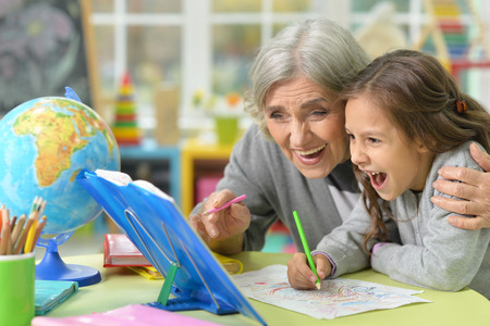 potrait: Potrait of grandmother with her granddaughter drawing