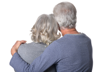 Rear view of  senior couple  hugging isolated on white background