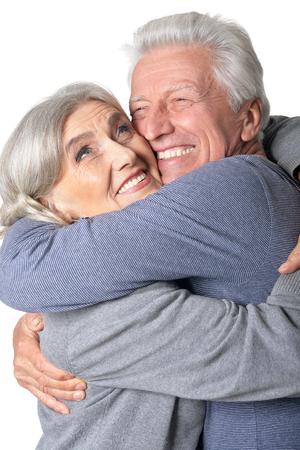 Portrait of hugging senior couple isolated on white background