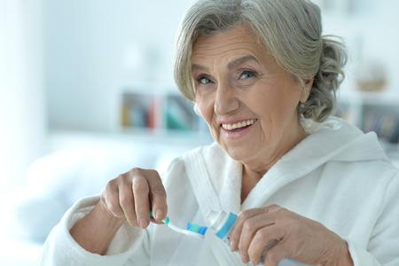 Portrait of happy senior woman brushing her teeth Imagens