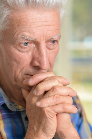 amiable: Portrait of thoughtful senior man with clasped hands