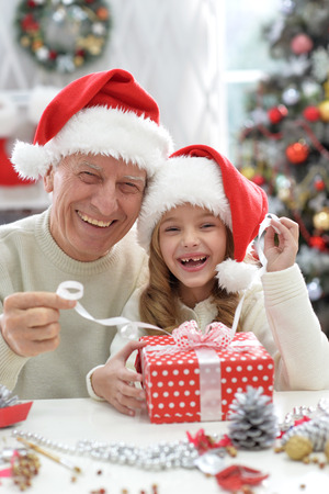 Portrait of  happy grandfather and child in Santa hats with Christmas present
