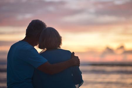 Gelukkige bejaarde paarrust bij tropisch strand bij zonsondergang, achtermening Stockfoto