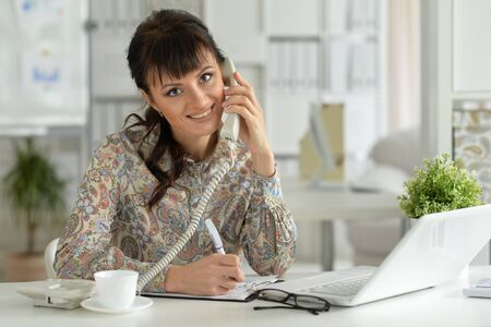 Portrait of young businesswoman talking on the phone in the office Stock Photo