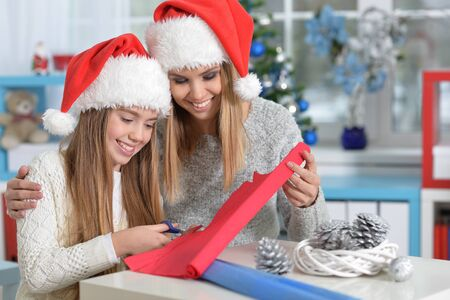 hapy: Portrait of  two hapy sisters in Santa hats preparing for Christmas cutting paper Stock Photo