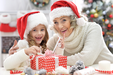 Portrait of exited grandmother and her little cute granddaughter sitting at the table with Christmas gift Stock Photo