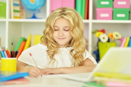 Cute  student girl  with book and laptop at class