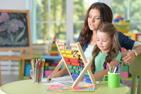 adds: Portrait of a girl doing math exercises with mother Stock Photo
