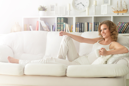 full lenght: Full lenght portrait of young beautiful woman with a cup of tea sitting on sofa at home