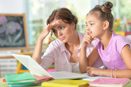 Portrait of a mother helping her daughter with homework 版權商用圖片