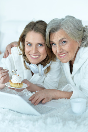 dring: Portrait of senior woman with her adult daughter eat tasty cake, dring tea and watching something on laptop