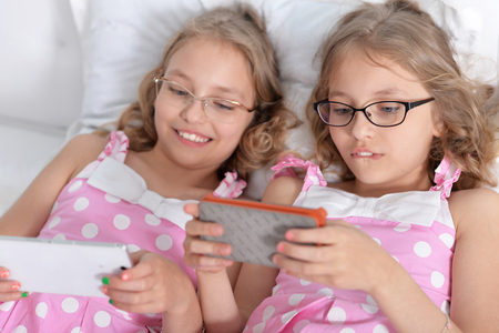 two sisters twins using smart phones, wearing eyeglasses