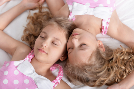 Portrait of two sisters twins sleeping together Stock Photo