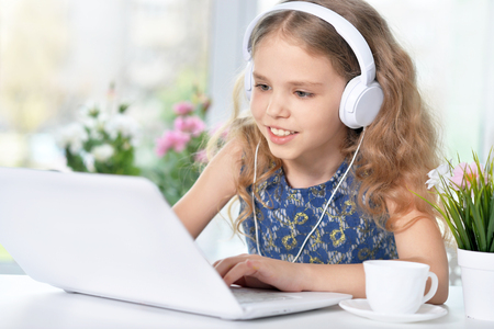 cute girl listening to music using headphones and laptop