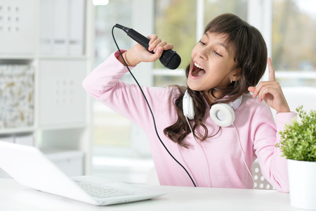 Portrait of a girl singing songs, using laptop