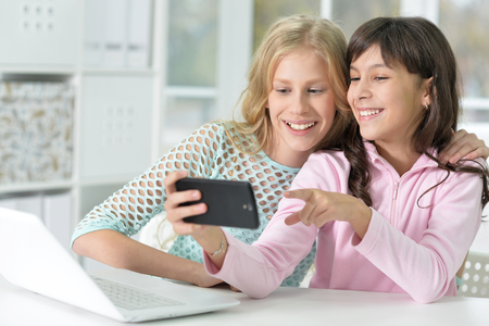 two girls with phone and laptop, using digital devices