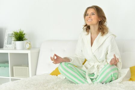 Young happy woman meditating sitting on her bed