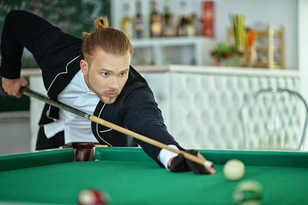cue sticks: Man playing billiards