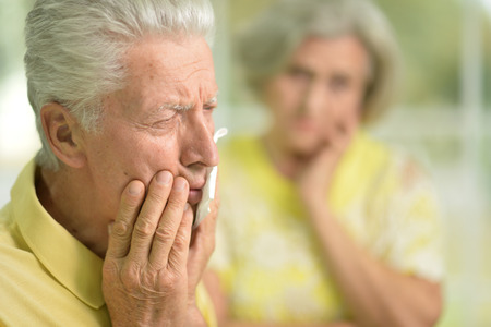 mature man having toothache, his wife Stock Photo