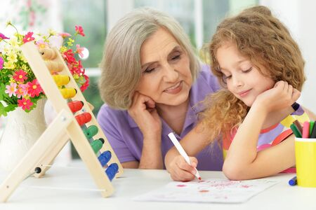 learning by doing: grandmother helping her granddaughter doing homework