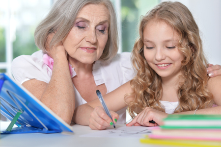learning by doing: grandmother and granddaughter doing homework Stock Photo