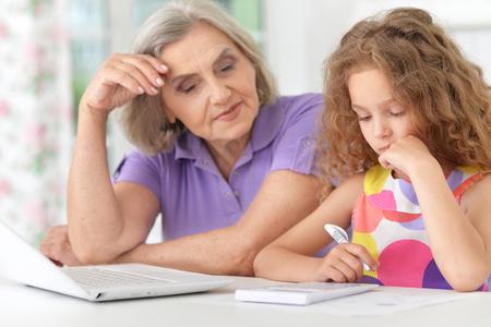 the elderly tutor: grandmother and granddaughter doing homework Stock Photo