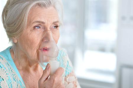 Sick elderly woman making inhalation