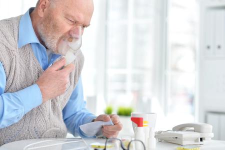 Sick elderly man makes inhalation