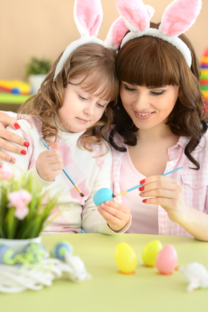 Mother and daughter paint Easter eggs