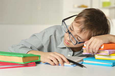Boy in glasses sleeps on books