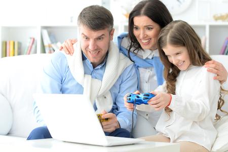 niños jugando videojuegos: Familia que pone un juego de ordenador Foto de archivo