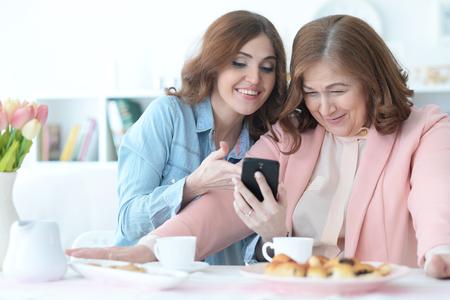 Dochter leert een oudere moeder om een mobiele telefoon te gebruiken Stockfoto