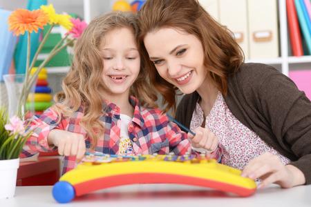 xilofono: Madre e hija están jugando en la mesa
