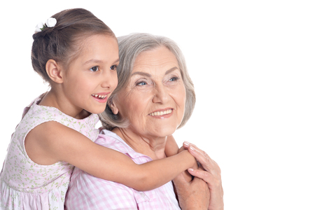 Grandmother and little granddaughter on white background