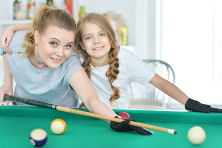 Mother with her daughter playing pool Banque d'images