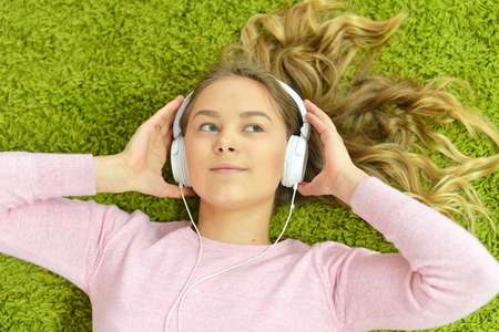 Girl lies on the floor and listens to music Stock Photo