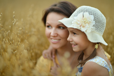 Mother with daughter on wheat field