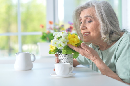 Beautiful old woman with flowers Stock Photo