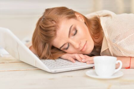 personable: young woman sleeping on floor with laptop Stock Photo