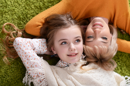 Mother and daughter lying on carpet