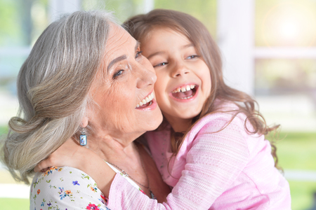 little girl hugging grandmother Stock Photo