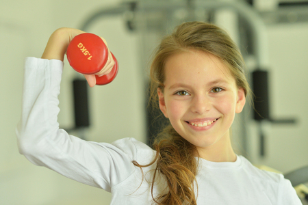 Little girl doing exercises with dumbbell in gym Stock Photo