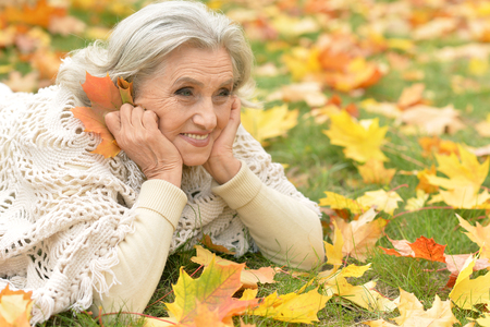 Beautiful senior woman lying on green grass with colorful autumn leaves Stock Photo